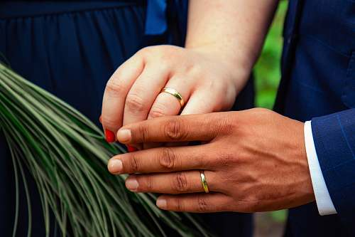 person two person with gold wedding bands in hands finger