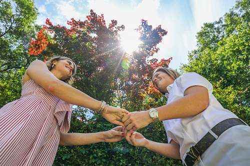 person two woman standing holding hands nature