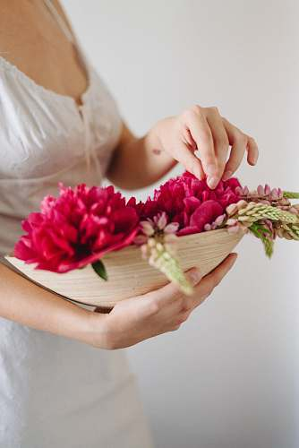 person woman carrying basket of flowers plant