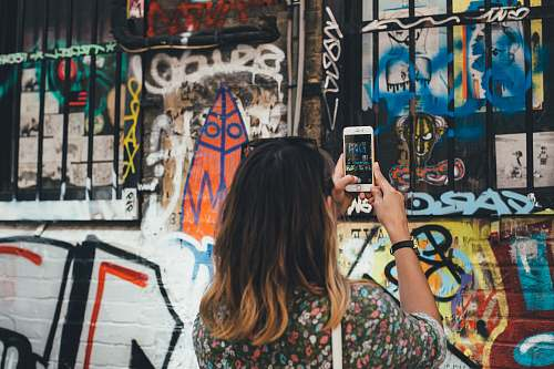 photo graffiti woman holding phone taking picture at wall phone free for commercial use images