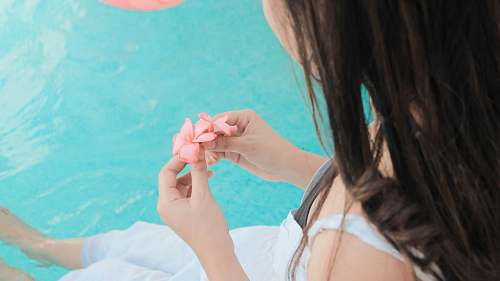 person woman holding pink petaled flower while both feet floats on water hand
