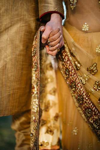 people selective focus of two person holding hands sari