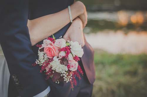 wedding woman holding flower bouquet while hugging man rose