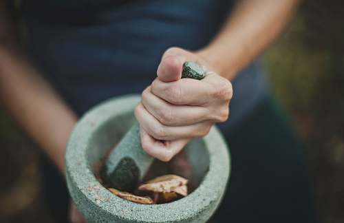 pestal person grinding on mortar and pestle grind