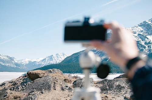 hand person holding camera distance with white mountains mountain