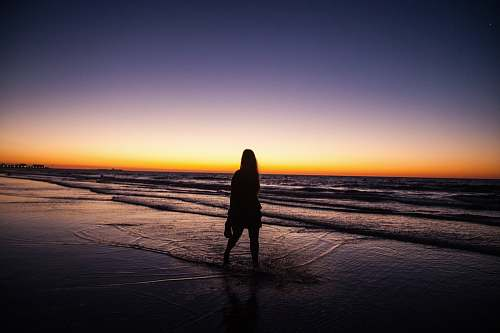 outdoors woman standing by the seashore under the sunset horizon