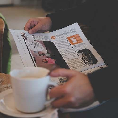 coffee person reading while holding white ceramic mug reading