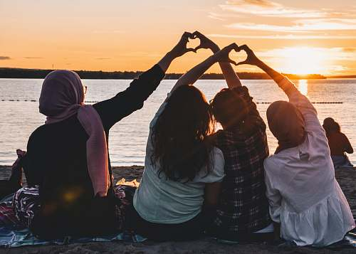 person four people sitting on shore forming hearts with their hands during golden hour human
