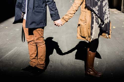 person man and woman standing while holding hands at daytime couple