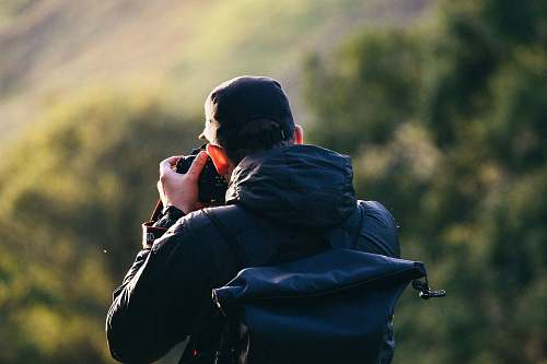 person man standing near mountain cliff while taking photo human