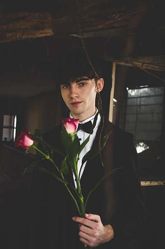 person man wearing black and white formal suit holding two red roses human