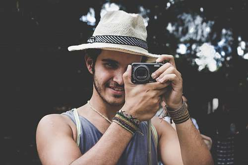 human selective focus photo of man holding black compact camera person