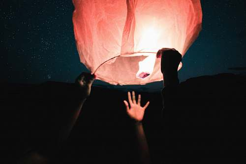 human three human hand about to catch and hold sky lantern at night time person