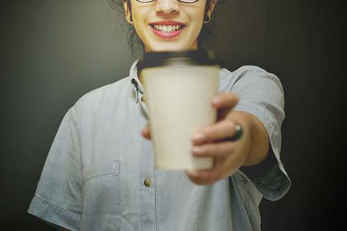 human woman holding white and black coffee cup person