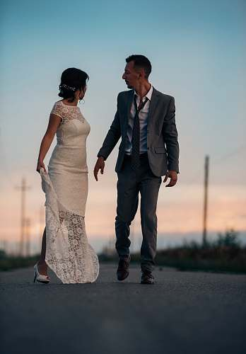 person woman in wedding dress beside man in gray suit jacket human
