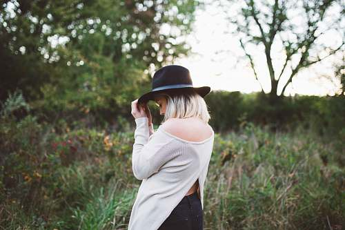 person woman in white off shoulder long sleeved top holding black hat girl