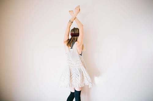 human woman wearing white sleeveless top with hands above head dance