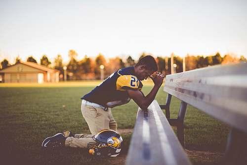 people baseball player kneeling on ground bench