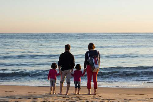 human family of four standing at the seashore outdoors
