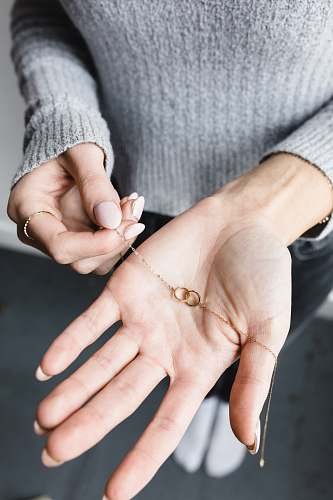 human gold-colored necklace finger