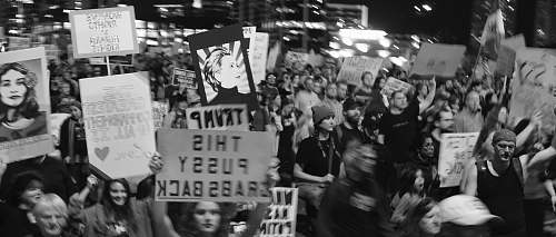 black-and-white grayscale photo of people holding signages crowd