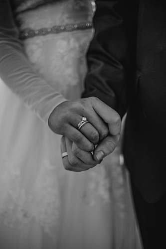 human grayscale photography of man and woman holding hand black-and-white