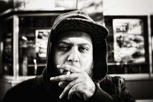 people grayscale photography of man holding cigarette portrait