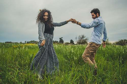 human man and woman holding hands on green field nature