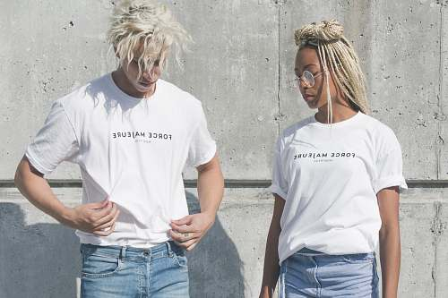 human man and woman in white-and-gray force majeure-printed crew-neck t-shirts standing near gray concrete wall people