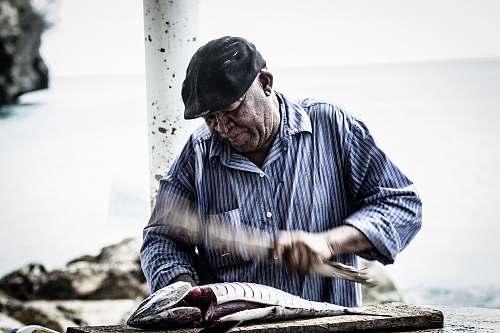 people man cutting raw fish using knife human