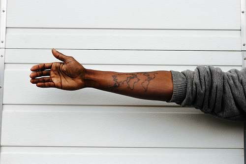 arm man raising hand with map arm tattoo behind white painted wall map