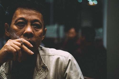 human man smoking cigarette during nighttime people