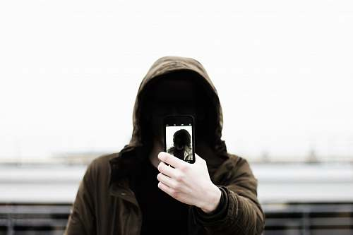 human man wearing black hooded jacket and holding smartphone white taking close-up selfie people