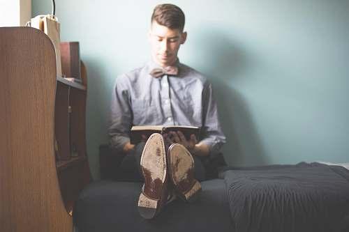 reading man wearing gray dress shirt reading book shoe