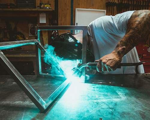 people man welding two rectangular gray metal frames human