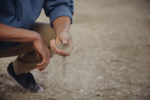 human Person crouches down with a handful of sand that slips through their fingers people