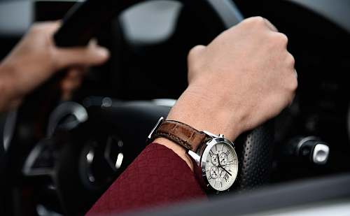 watch person driving car with black steering wheel wrist watch