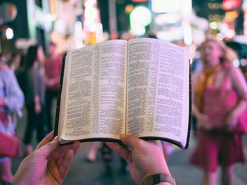 new york person holding bible on road with people walking on sidewalk beside buildings during nighttime bible