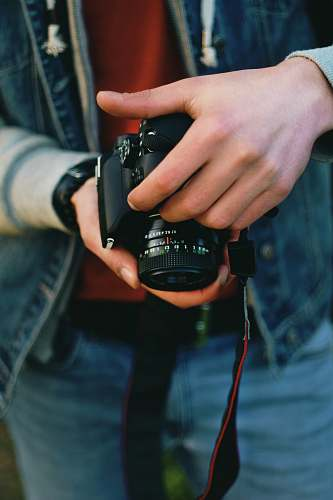 human person holding black Canon DSLR camera people