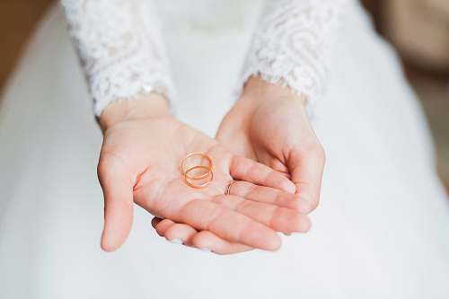 wedding person holding copper rings during daytime wedding ring
