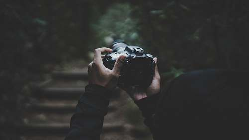 human person holding DSLR camera people