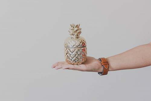 human person holding gold-colored pineapple design rack wristwatch