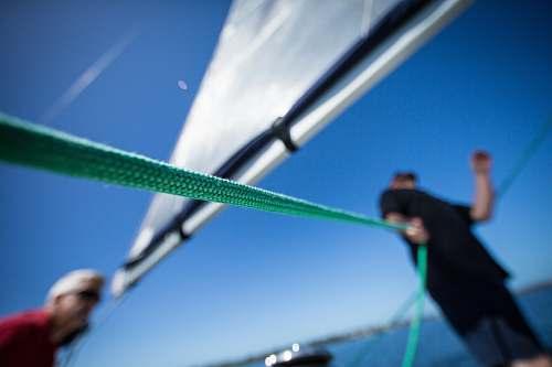 sailing person holding green rope near boat sail human