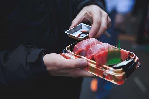 human person holding tuna sashimi food