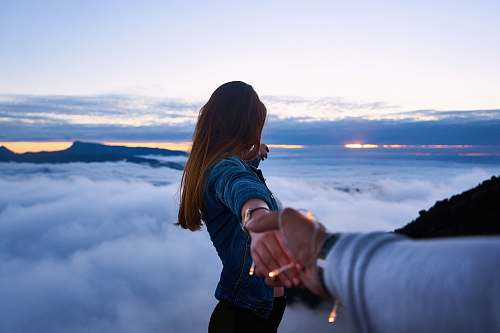 people person holding woman's hand on top of hill couple