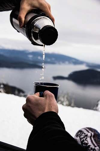 human person pouring water in black ceramic mug people