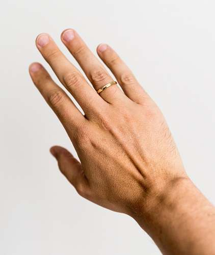 human person showing gold-colored ring hand