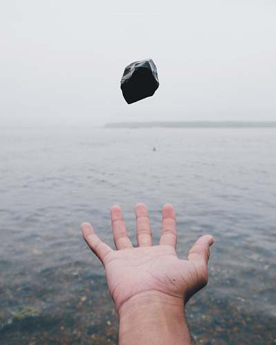 human person throwing black stone on water hand