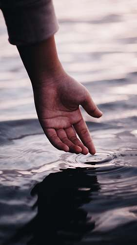 human person touching body of water water