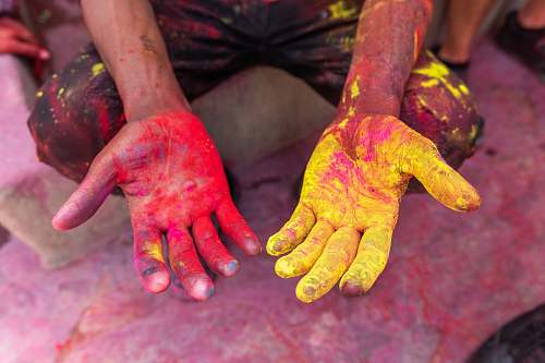 human person's hand with yellow and red powder hand